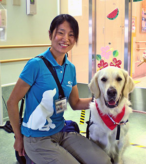 Facility dog handler Yuko Morita and Bailey visit children in hospital.