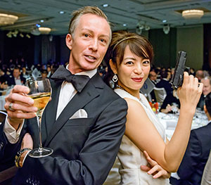 Masters of Ceremony Guy Perryman and Madoka Kato pose in James Bond style.