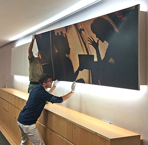 Richard Morgan installs a graphic for a client.