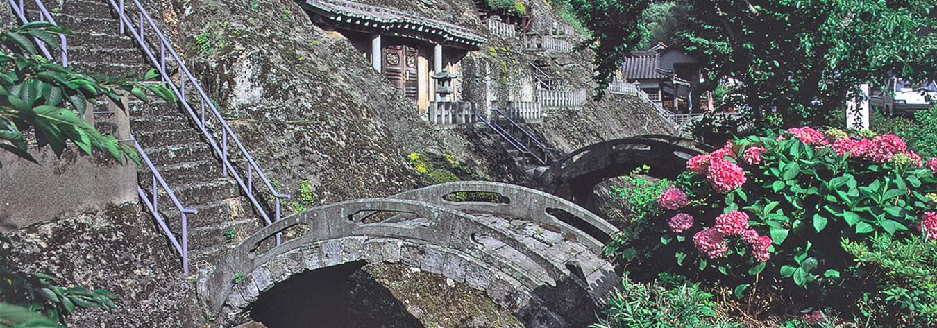 Rustic stone bridges lead to statues at Rakan-ji Temple.